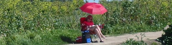 Lady with umbrella chair on a Costa Mesa dirt trail