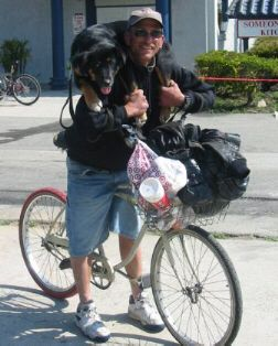 Man Riding Bicycle Carrying Large Dog on His Shoulders