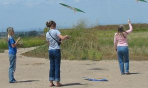 Mom & two daughters flying kites on the Costa Mesa dirt trails